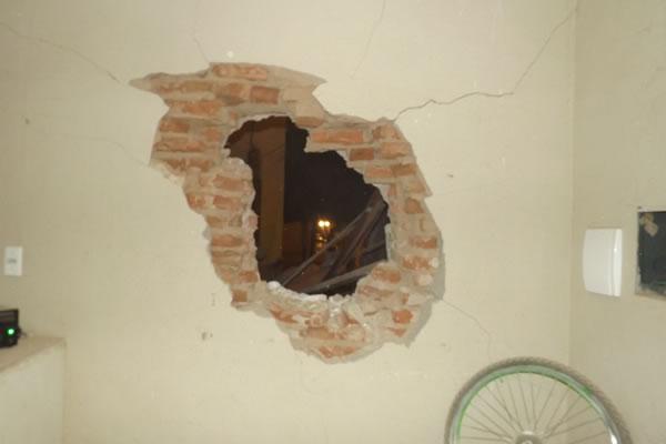 Uma das portas do caixa atravessou uma parede e caiu dentro do destacamento de polícia (Foto: Na Rota da Notícia)