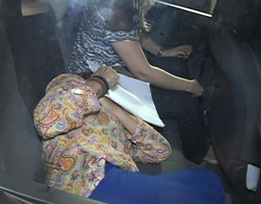 Cristiane se entregou à polícia e cobriu o rosto durante deslocamento (FOTO: Reprodução TV Jangadeiro)