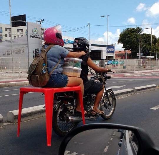 Motocicleta transporte passageira sentada em mesa de plástico em Fortaleza (FOTO: Reprodução Whatsapp)