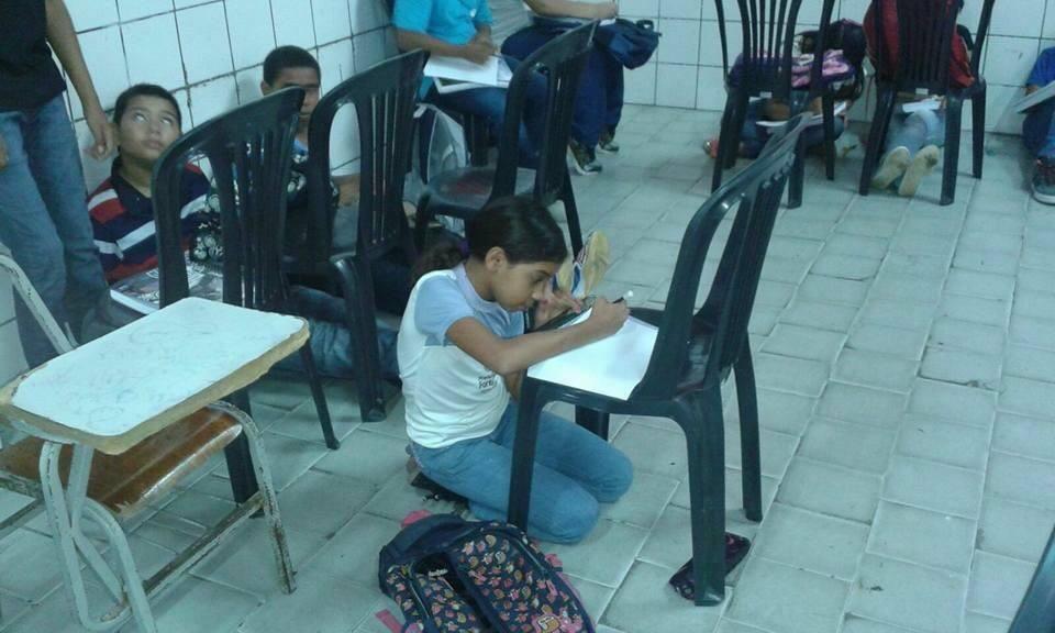 Alunos assistindo aula sentados no chão (Foto: Reprodução)