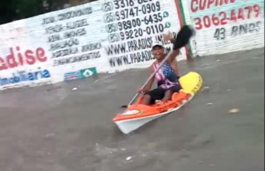 """Fortalezenses usam caiaque e prancha de surf para """"navegar"""" em alagamento de Fortaleza"""