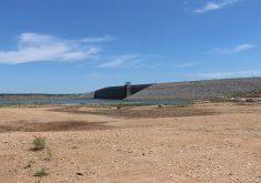 Foto da parede do açude Castanhão com maior parte de terra e pouca água. Foto de Jéssica Welma, do Tribuna do Ceará