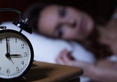 Mulher acordada deitada na cama enquanto o relógio marca 3h da manhã