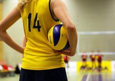 Atleta segurando bola de vôlei no braço