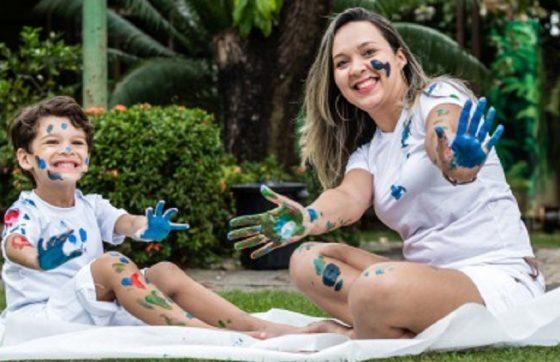Mãe e filho fazendo pinturas referência as atividades do mês do autismo
