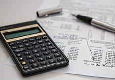 Calculadora, caneta e papel com números.