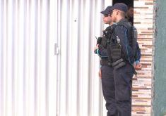 Dois policiais em frente à residência da família onde pai matou o filho