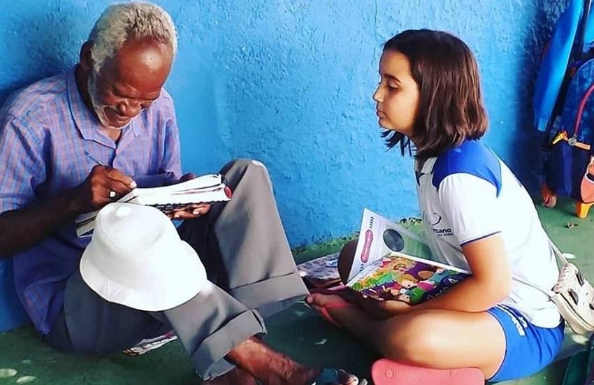 Criança ensina vendedor de picolé a ler e a escrever em chão de pátio da escola