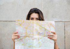 jovem-viajante-feminino-espreitando-por-tras-do-mapa_1262-5958