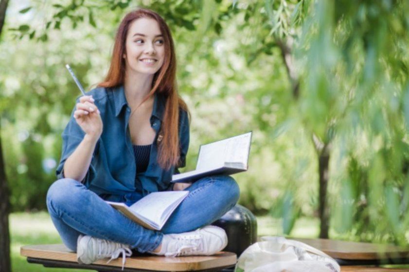 menina-feliz-estudando-no-parque_23-2147657042