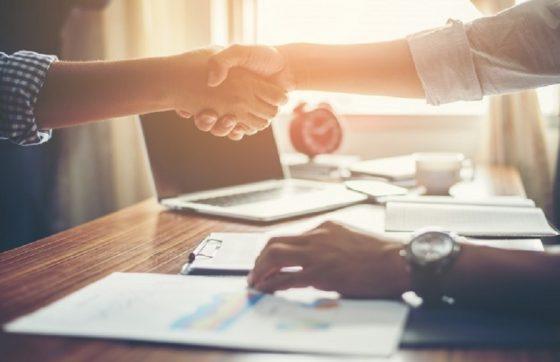 Duas mãos fazendo referência a fechar negócio em um escritório