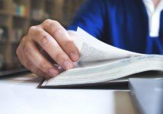 Mão de um homem passando a página de um livro