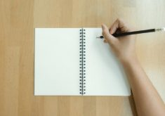 Mão escrevendo no caderno em referência a cursos na Cagece