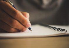 Mão escrevendo no notebook em referência a estágio em turismo na Prefeitura de Fortaleza
