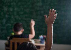 Garoto levantando a mão em escola