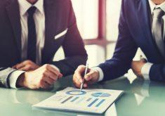 Homens de terno em uma mesa em referência a Escola de negócios oferta curso que desenvolve habilidades de liderança e gestão