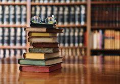 Livros empilhados com óculos em cima