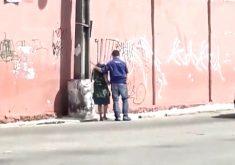Leonardo Lopes ajuda idosa a atravessar a rua (FOTO: Reprodução TV Jangadeiro)